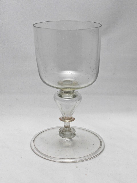 Facon de Venise Wine Glass from Elizabeth and Theo Zandbergen from northern Netherlands 17th Century. This fine wine glass has a so called rounded bucket bowl, see Bickerton, which is an almost cylindrical cup slightly, rounded of at the bottom. A bucket bowl is one of the rarer forms for this type of glass. The very large diameter foot is also quite typical for glasses from this period see also the glass with the two hollow knops. The cup set directly on a merese which on a second smaller merese and then attached to the top part of the pointed hollow knop. At the bottom part of the knop is again a small merese, followed by a short solid section connecting thru a flattened knop to the almost flat foot with turned in rim. The stem construction is a so called inverted baluster.