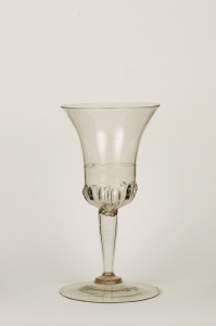 """Stem Type: A tall hollow """"a jambe"""" meaning like a leg or cigar-shaped stem rests on a merese (collar).  Description: Cristallo wine glass has a bell-shaped bowl decorated with gadrooning and a thin clear glass thread circling the center. The tall hollow """"a jambe"""" meaning like a leg or cigar-shaped stem rests on a merese (collar)  attached to a wide circular foot.32E Venitian WineGoblet"""