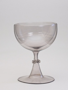 Stem definition: Hollow trumpet shaped stem which starts as a broad foot. A pincered collar is applied to the narrow part of the stem near the double-walled bowl. The goblet has a grayish-lilac tint.89E TrickGlass