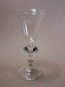 Stem Definition: a compound repeating pattern of a small hollow knop attached larger hollow knop separated by a merese with two pinched (blue) ornaments  Description: The stem of this Liege Façon de Venise glass has a restrained exuberance characteristic for that time for the Southern Netherlands but, is still quite vivid from the two pinched blue ornaments. The spiralled trumpet optically blown bowl is set via a merese to the first small hollow knop directly followed by the largest somewhat flattened hollow knop to which the blue ornaments are attached. Followed by a merese connecting to a concave formed transition piece set to another hollow knop followed by a merese connecting to a short solid section which connects to the conical foot. glas #55